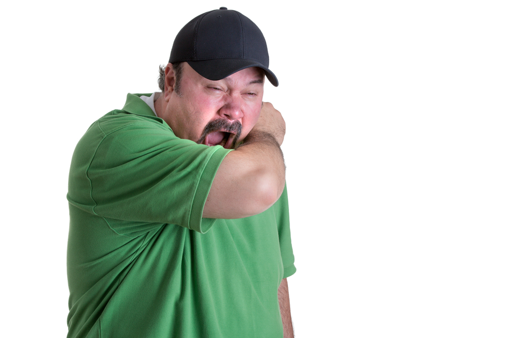 man covering mouth when sneezing